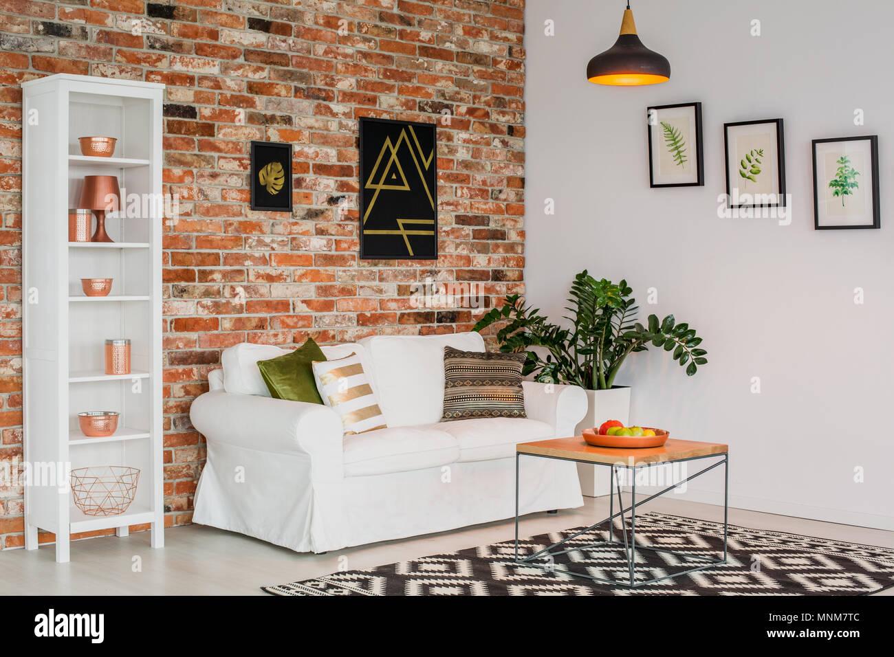 Semplice soggiorno con mobili bianchi, muro di mattoni e la moquette ...