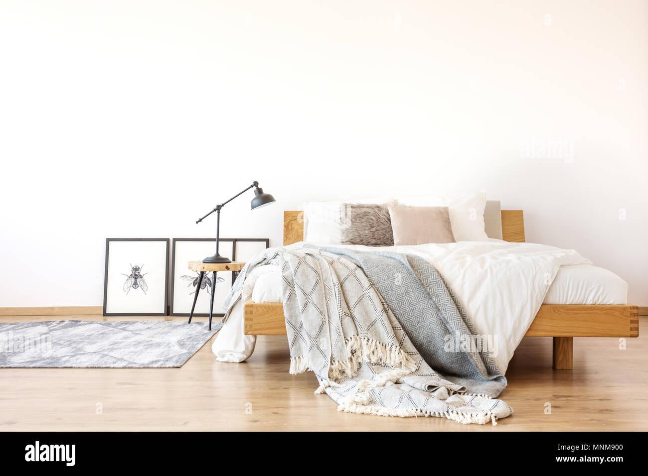 Lenzuola su legno letto king size contro il muro bianco in camera