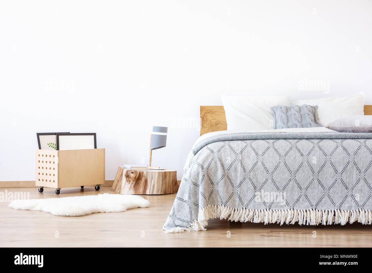 Lampada di design sul moncone di legno e tappeto bianco in camera