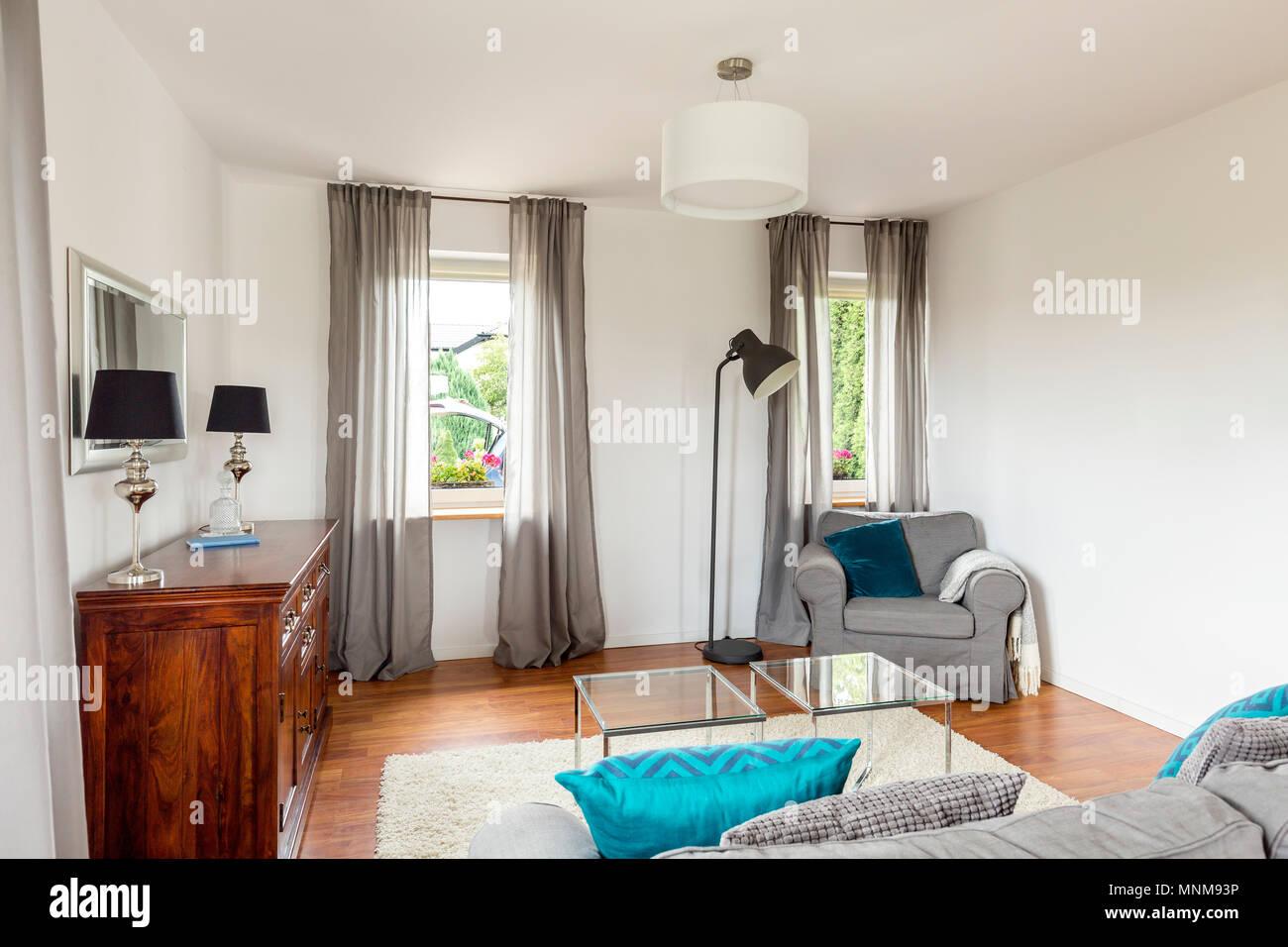 Piccolo soggiorno con elegante dresser, tavolo di vetro, divano e di ...