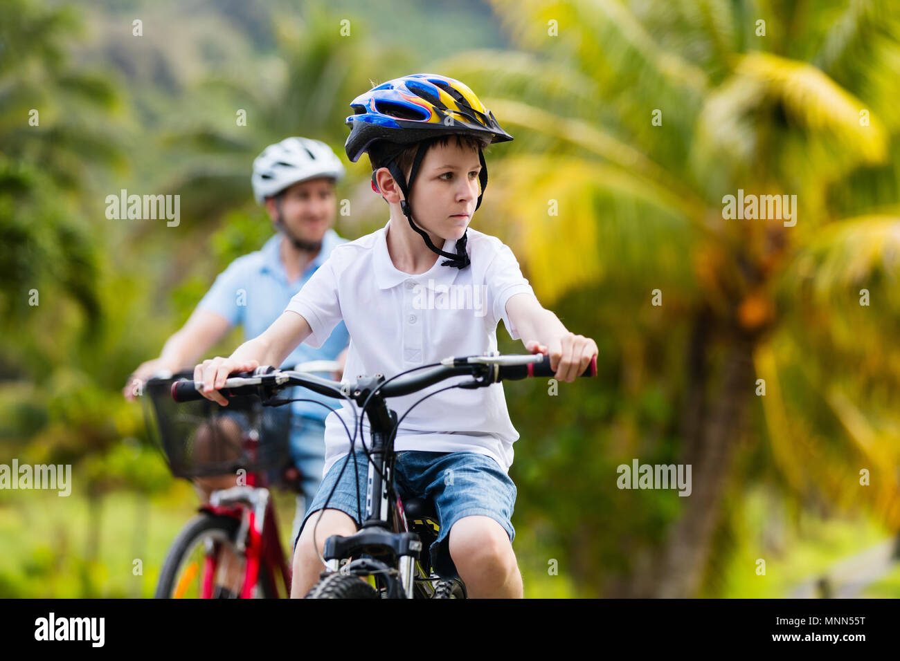 La famiglia del padre e figlio bike a impostazioni tropicale Immagini Stock