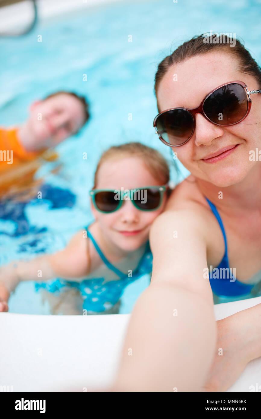 La famiglia felice la madre e i suoi bambini in piscina all'aperto tenuto selfie sulla vacanza tropicale Immagini Stock