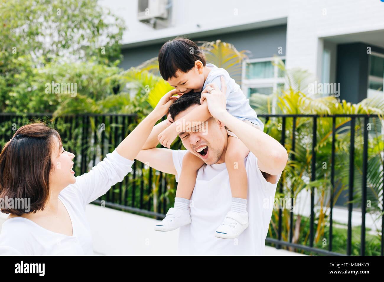 Carino padre asiatici piggybacking suo figlio insieme con sua moglie nel parco. Famiglia entusiasti di trascorrere del tempo insieme con la felicità Immagini Stock