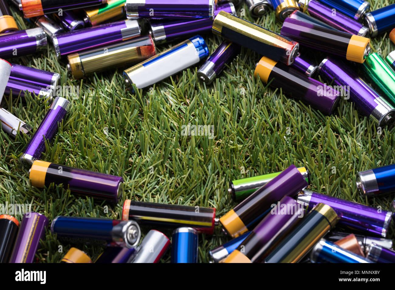 Vista in elevazione delle batterie utilizzate su erba verde Immagini Stock