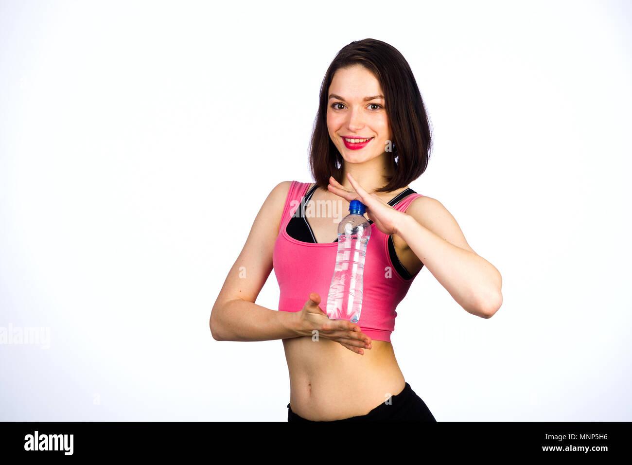 Ragazza giovane con una bottiglia di acqua potabile su uno sfondo