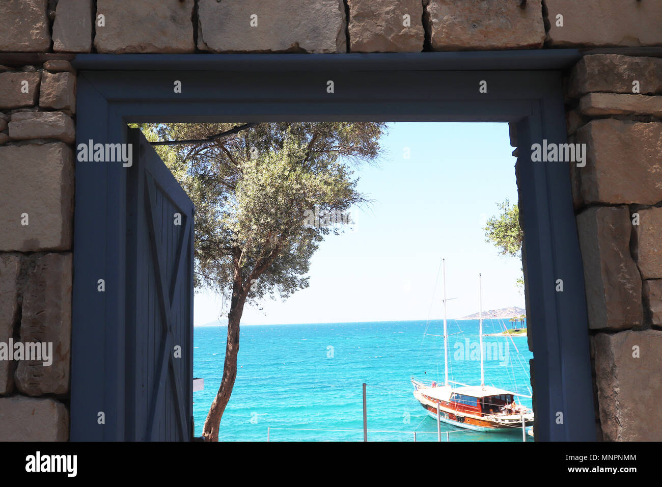 Mare Egeo dietro lo sportello blu con muro di pietra Immagini Stock