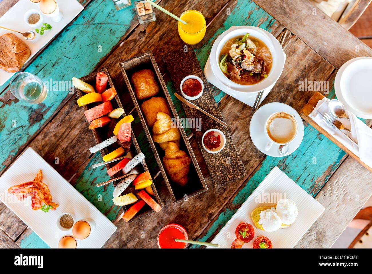 Vista superiore del delizioso cibo organico serviti per colazione sulla tavola in legno rustico. Caffè, uova, frutta, succhi di frutta, cornetti e marmellata. Immagini Stock