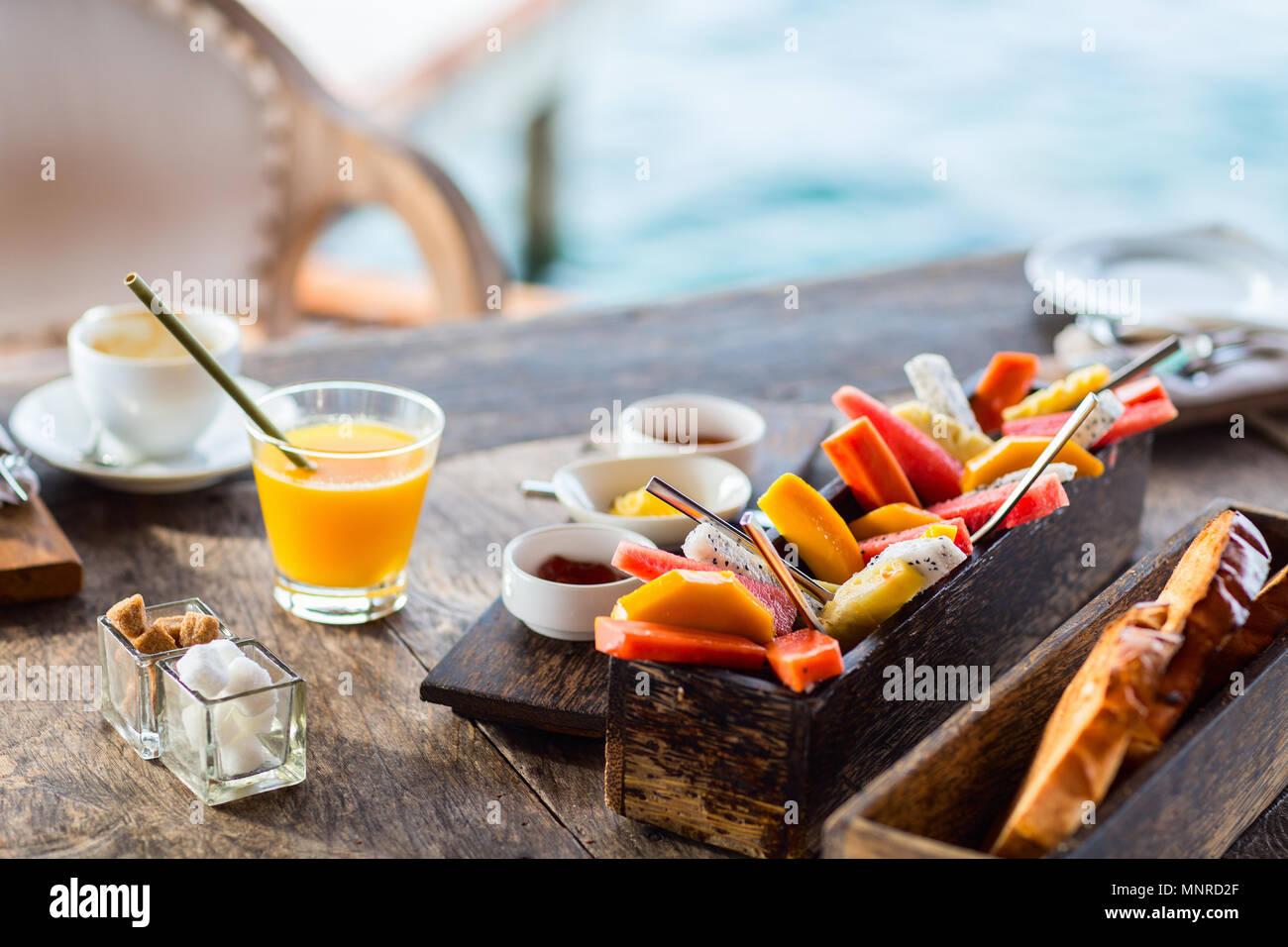 Close up di deliziosi cibi biologici serviti per colazione sulla tavola in legno rustico. Frutta, succhi di frutta, pane e marmellata. Immagini Stock