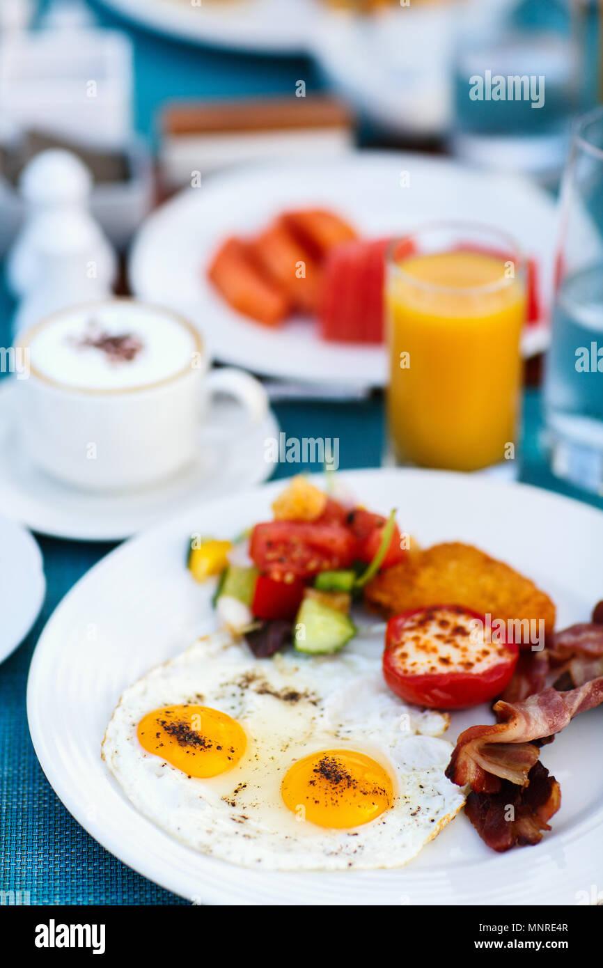Deliziosa colazione a buffet con uova fritte, pancetta e verdure Immagini Stock