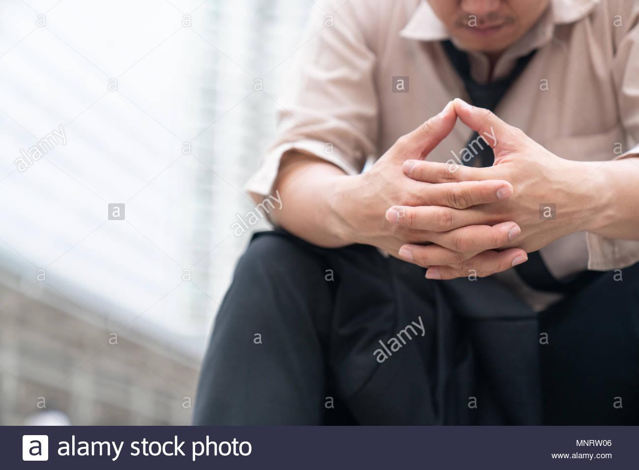 Stanco o stressato imprenditore seduta sul marciapiede in città dopo il suo lavoro. Immagine di imprenditore ha sottolineato concetto. Immagini Stock