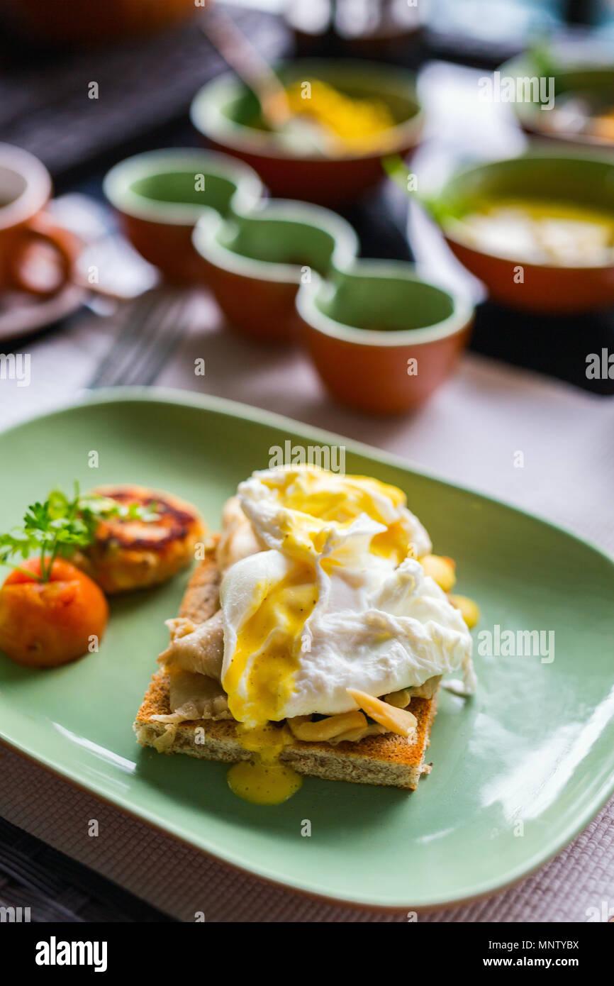 La colazione tabella riempita con assortimento di cibo. Le uova in camicia, Sri Lanka curry e tè Immagini Stock