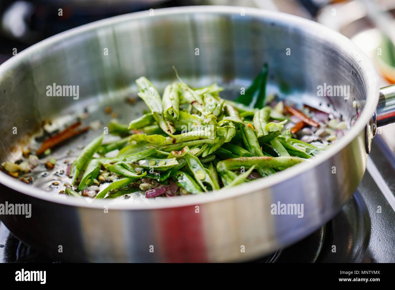 Preparazione di tradizionali dello Sri Lanka il piatto con i fagiolini verdi a lezioni di cucina Immagini Stock