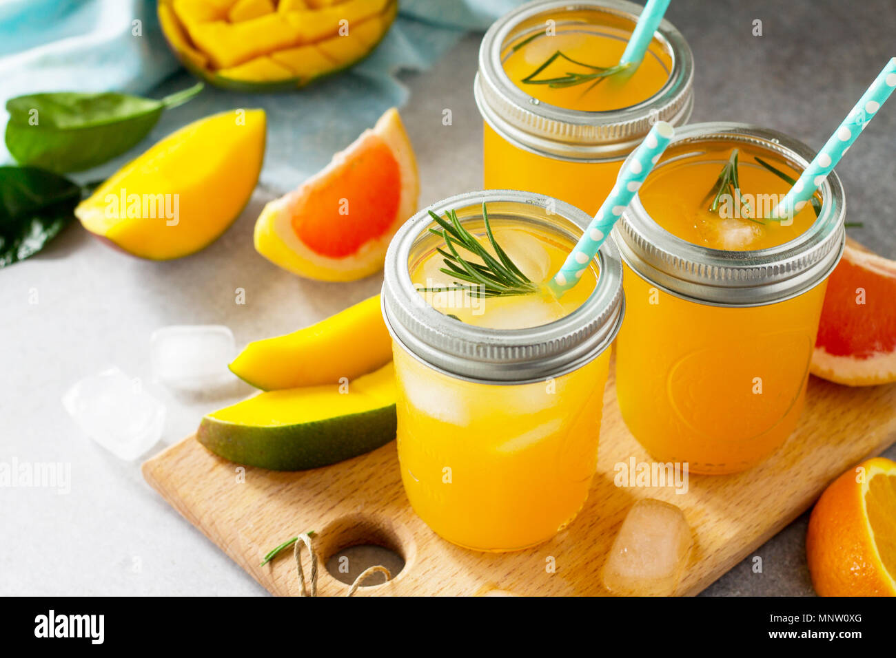 Rinfrescanti cocktail estivi fatti di agrumi e di mango, bevanda fredda o un drink con ghiaccio su uno sfondo nero. Concetto di cibo vegetariano, fresche vitamine Immagini Stock