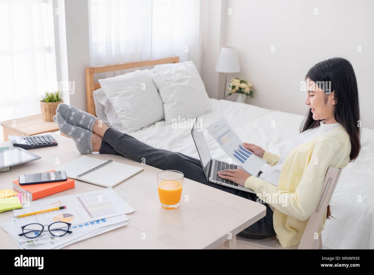 Femmina asiatica del freelancer report di lettura di carta e di lavorare con il computer portatile giaceva sul ginocchio con il resto della gamba sul tavolo in camera da letto a casa.Il lavoro a casa concetto.lavoro f Immagini Stock