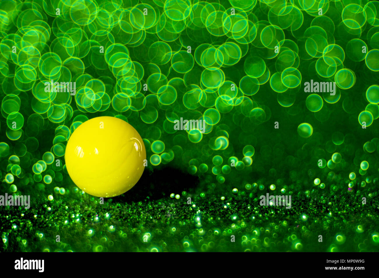 Vivida sfera gialla con un vivace verde sfondo bokeh di fondo. Immagini Stock