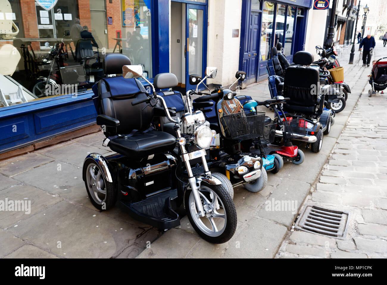 Un assortimento di sedie a rotelle elettriche al di fuori di un negozio di mobilità in Chesterfield, Derbyshire, Inghilterra Immagini Stock