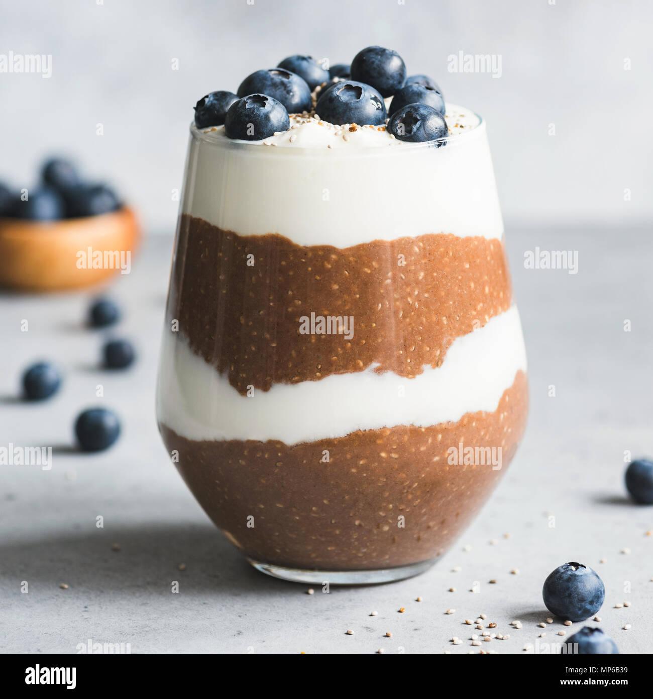 Layered cioccolato budino di Chia con yogurt e mirtilli in un bicchiere. Vista ingrandita, quadrato ritaglia Immagini Stock