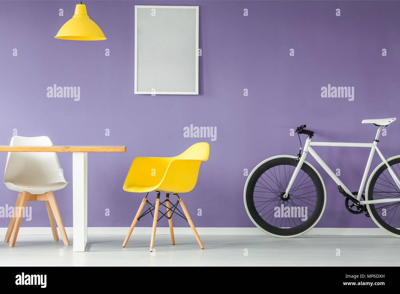 Minima, interni moderni con un bianco e giallo sedia, una bicicletta, una tabella vuota e appeso un lampada gialla contro sfondo viola parete con una simulazione Immagini Stock