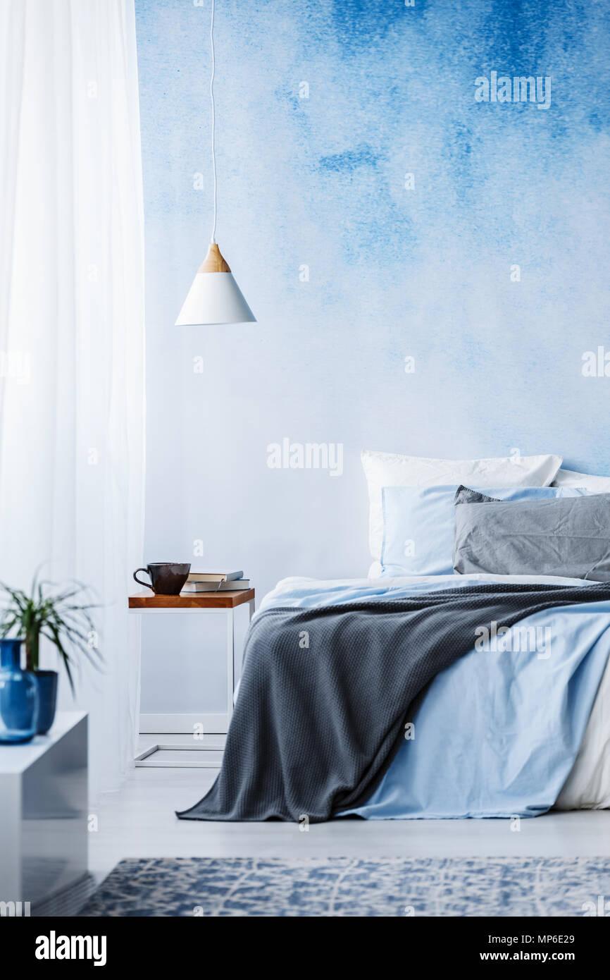 Blu e grigio un lenzuolo sul letto contro la parete di ombre in ...