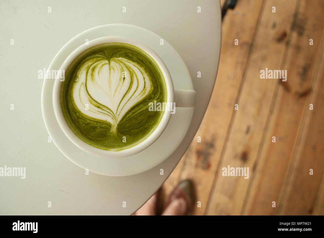 Una tazza di tè matcha con belle latte art su una tabella grigia in una caffetteria. Immagini Stock