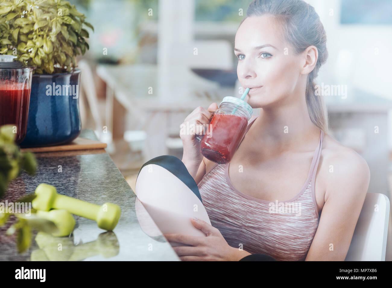 Sportive sulla dieta detox corpo purificante bevendo rosso sano cocktail dopo la ginnastica Foto Stock