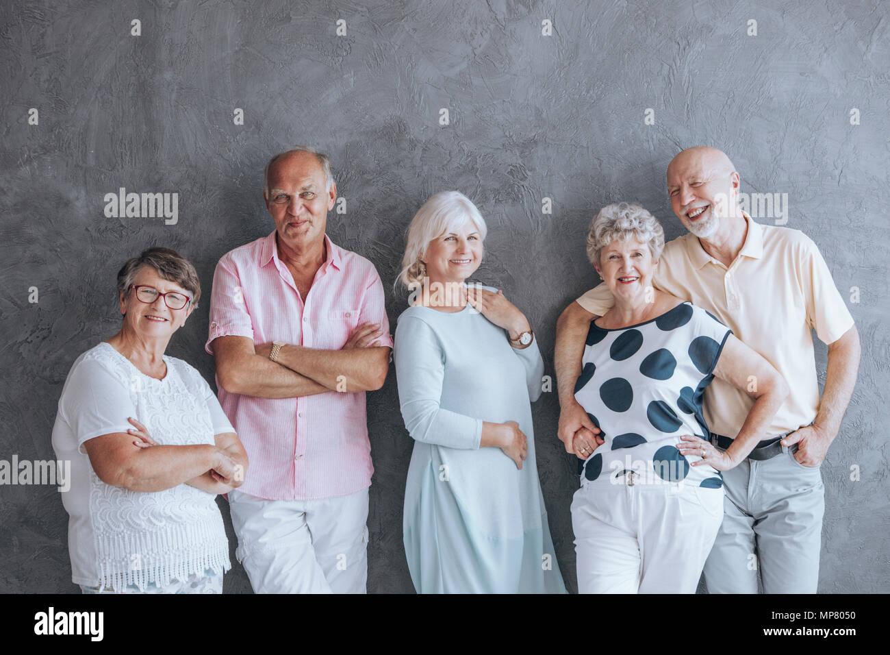 Felici le persone anziane in abiti casual contro il muro di cemento. Seniors concetto amicizia Immagini Stock