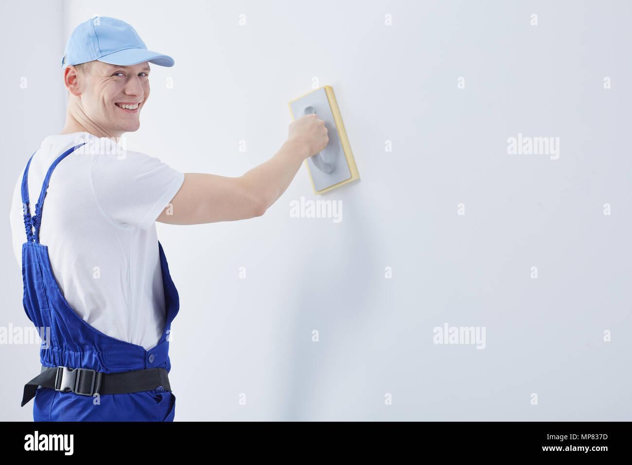 Bello felice giovane uomo che lavora come una costruzione interna lavoratore Immagini Stock