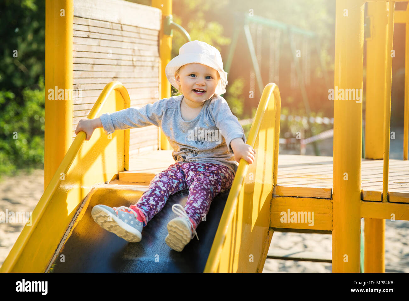 Sorridenti bambino sul cursore, al parco giochi all'aperto Immagini Stock
