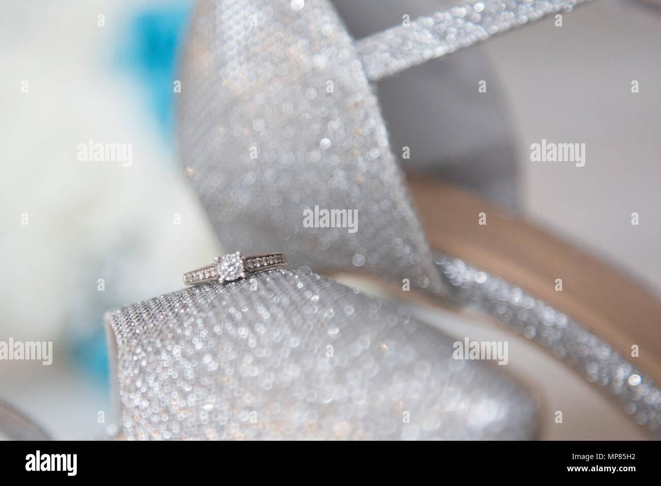Anello di fidanzamento seduto su una coppia di scintillanti di bridal scarpe lucide il giorno delle nozze d'argento, scarpe e corona diamantata Immagini Stock