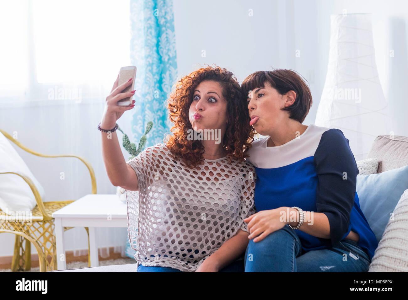 Due giovani donne a scattare foto con il cellulare a casa facendo bello e divertente di espressioni. migliori amici che l amore per comunicare in rete con frie Immagini Stock