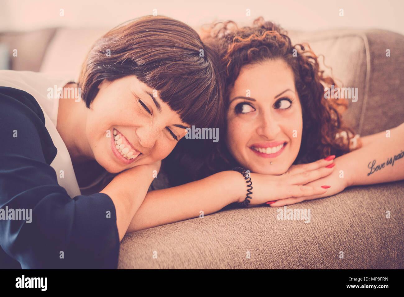 Bel tempo e felicità con ridere e sorrisi per due amici caucasici stabiliscono insieme sul divano di casa. Il concetto di amicizia per immagine interna w Immagini Stock