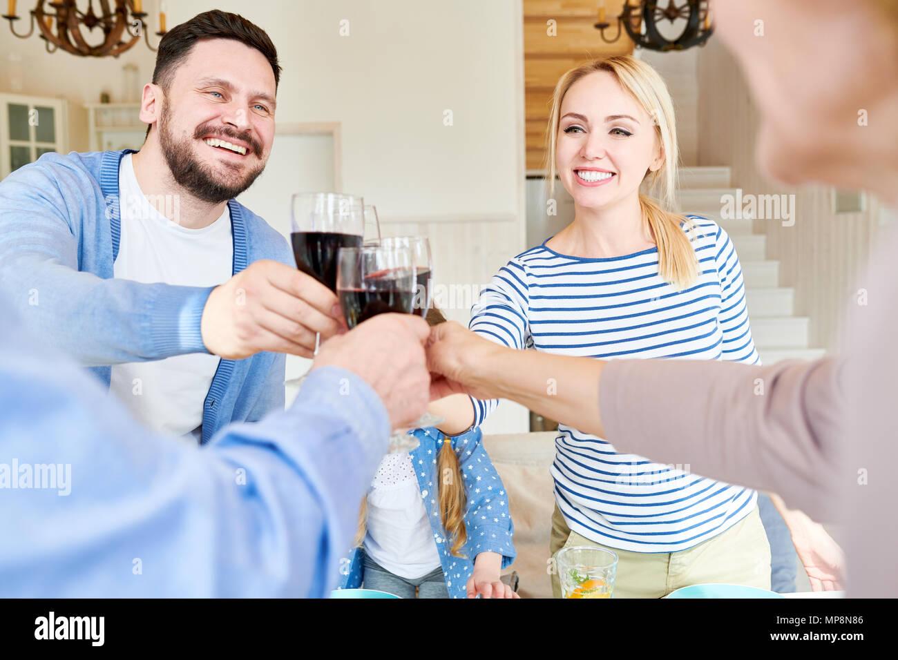 La famiglia bicchieri tintinnanti alla celebrazione di vacanza Immagini Stock
