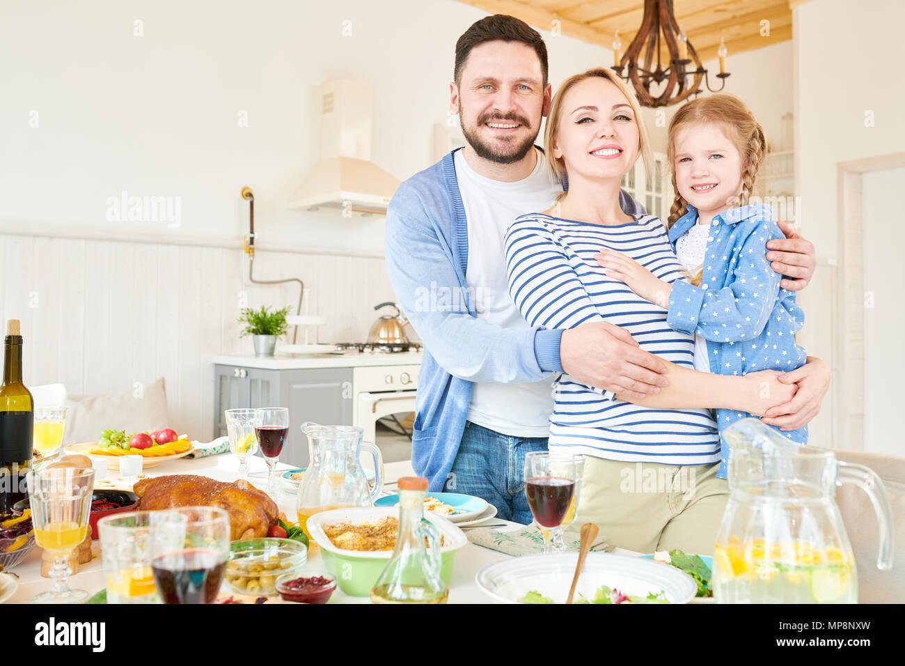 Il successo di giovani famiglie che pongono al tavolo per la cena Immagini Stock