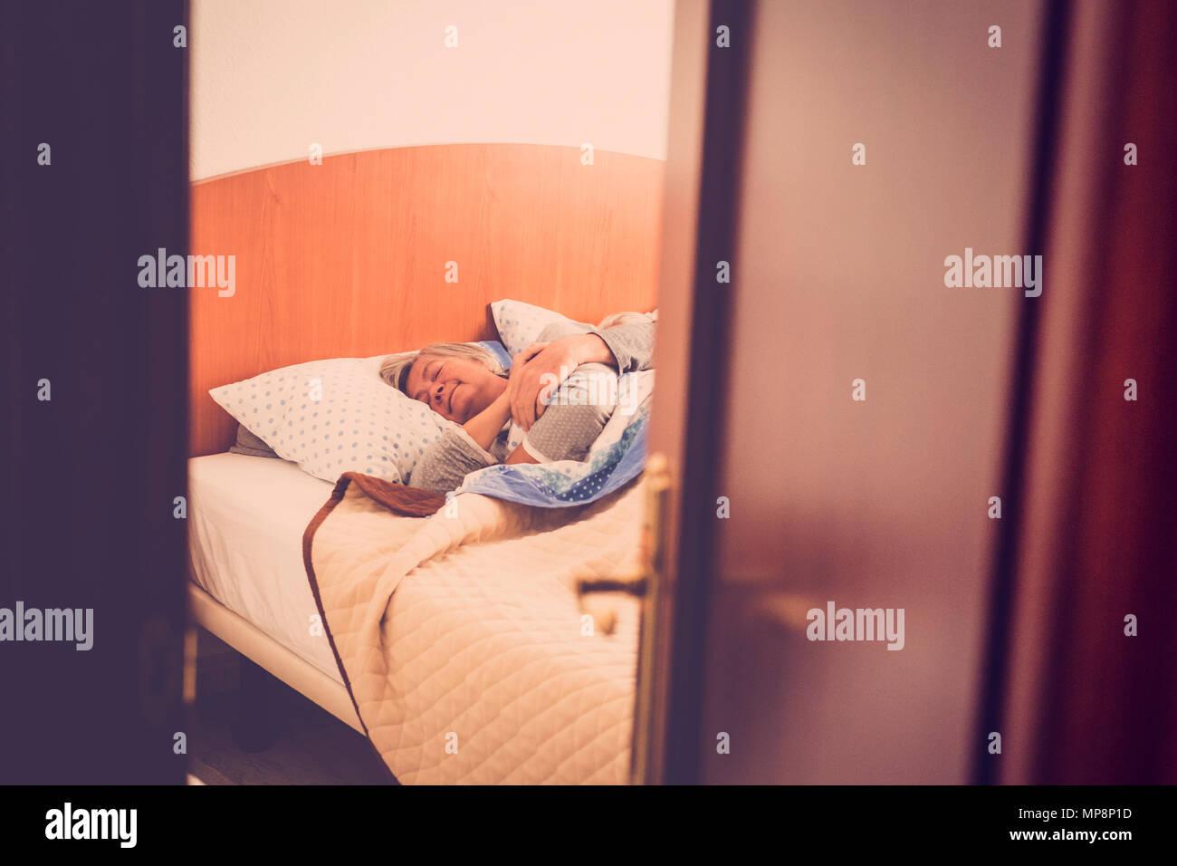 Adulto di età matura a dormire per la camera da letto di casa, indoor scena quotidiana per il dolce amore eterno. look rétro filtro. scena nascosta. dolcezza e anziani Immagini Stock