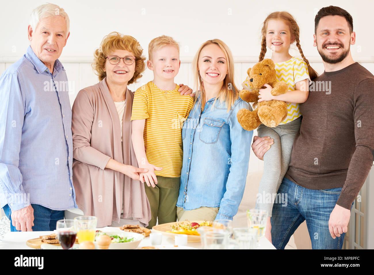 Due generazioni la famiglia in posa a casa Immagini Stock