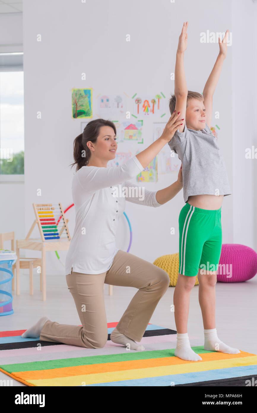 Inquadratura di un ragazzino a fare gli esercizi con la sua fisioterapista Immagini Stock