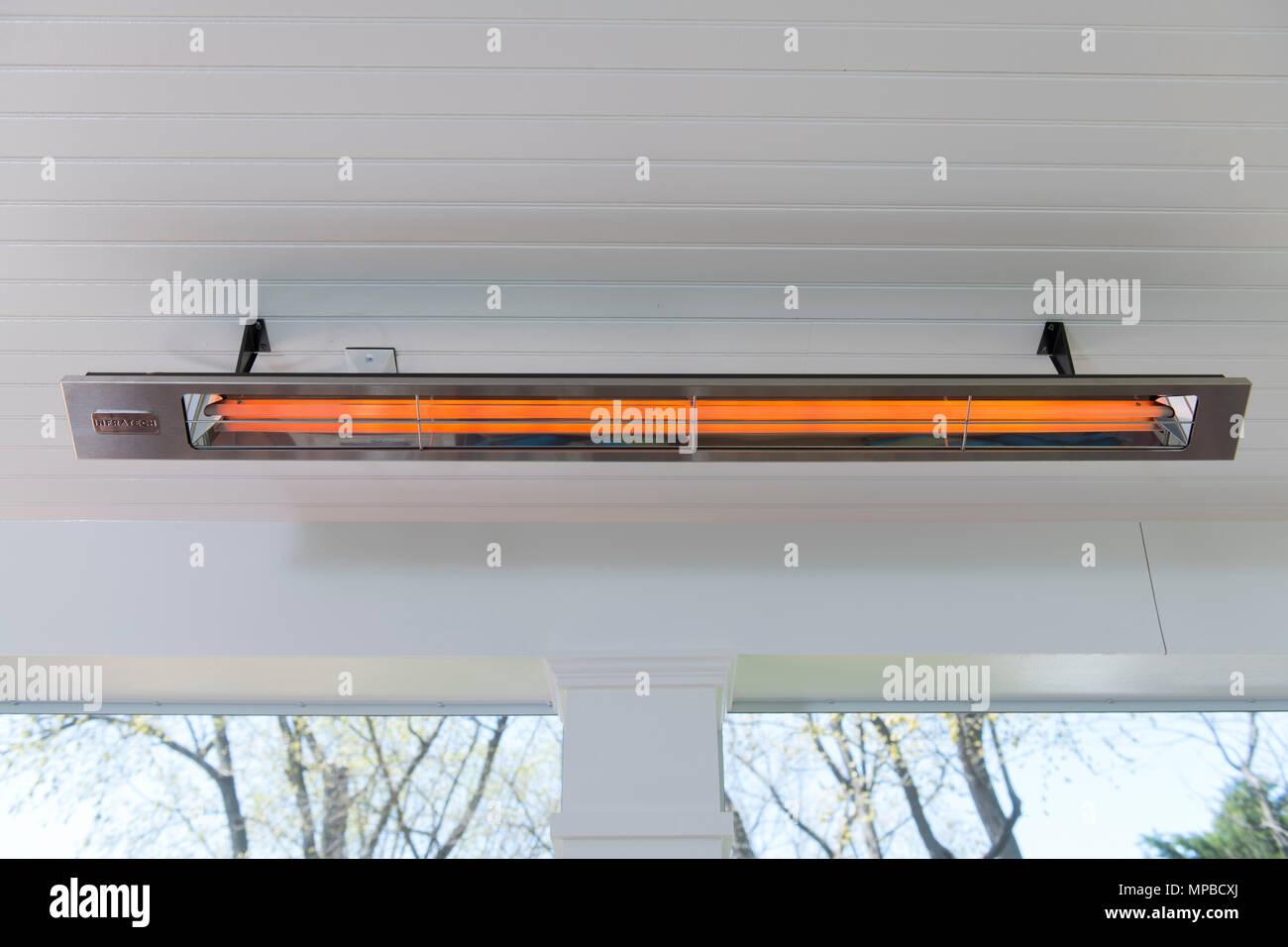 Un elettrico riscaldatore a raggi infrarossi su una veranda riparata fornisce il calore radiante nelle giornate fredde Immagini Stock