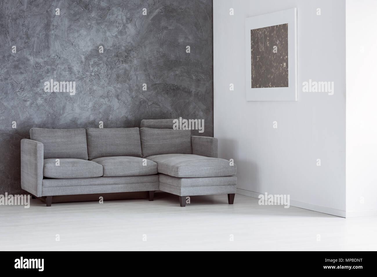 Soggiorno Con Divano Grigio Scuro vuoto semplice soggiorno con divano grigio contro il muro di