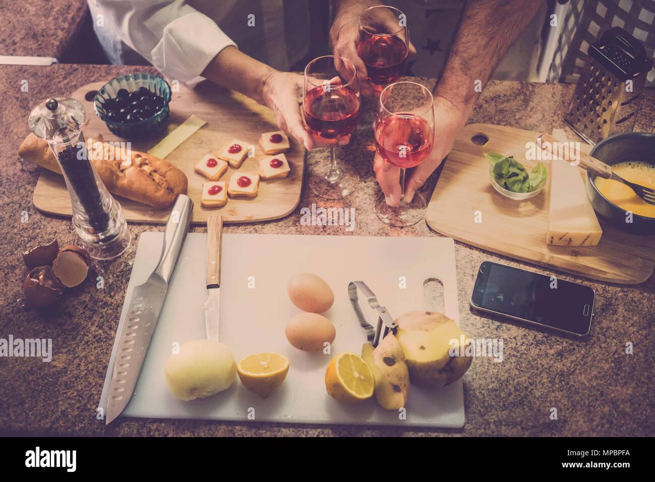 Tre persone vicino a mani sul tavolo durante un tempo di cottura a casa con la famiglia e gli amici. molti cibi crudi e il telefono cellulare. Immagini Stock