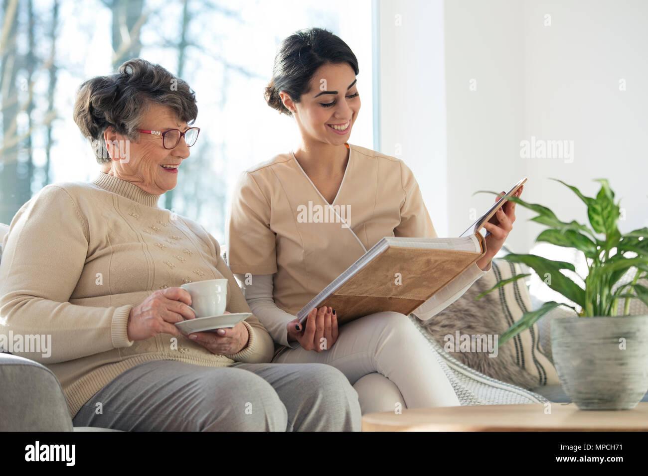 Sorridente custode professionale che mostra un album di famiglia di un anziano donna in un salotto di casa Immagini Stock