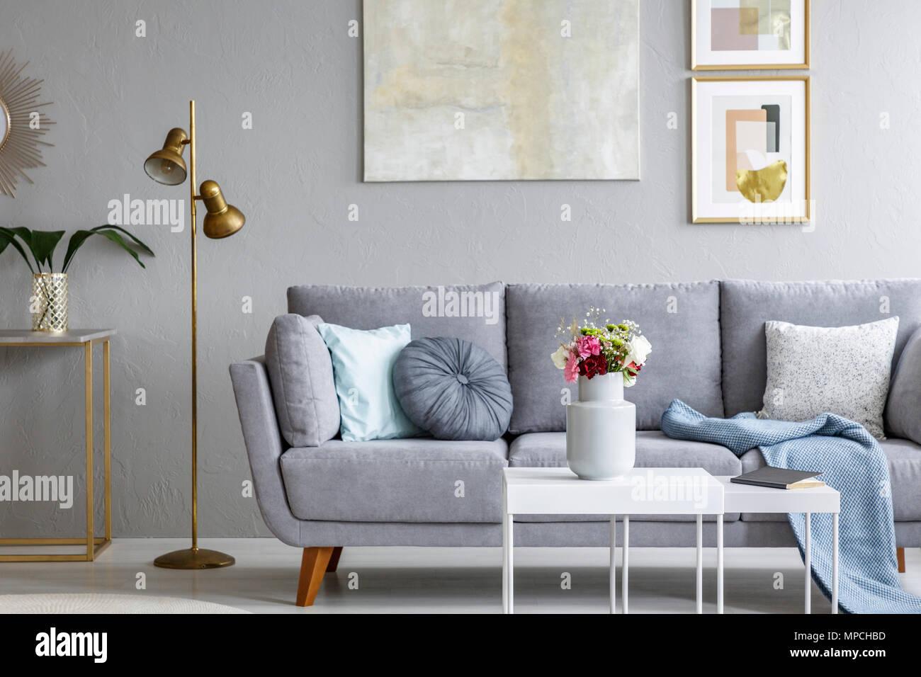 Oro lampada accanto al grigio divano nel soggiorno moderno interno ...