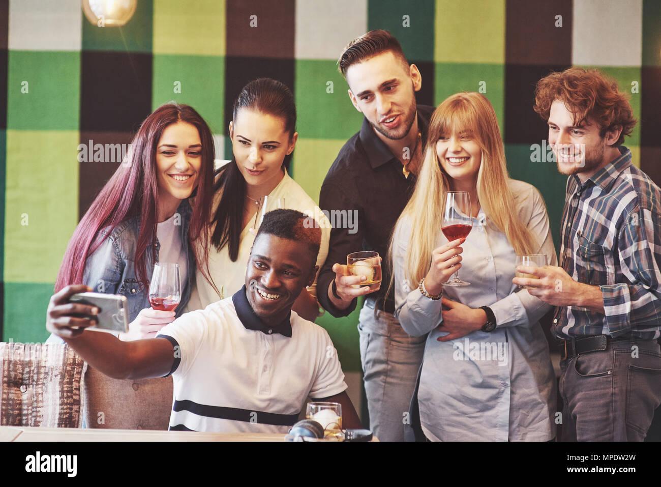 Amici divertendosi al ristorante.due ragazzi e 4 ragazze bere rendendo selfie, facendo segno di pace e di ridere. Sul primo piano donna azienda smart phone. Tutti indossare abiti casual Immagini Stock
