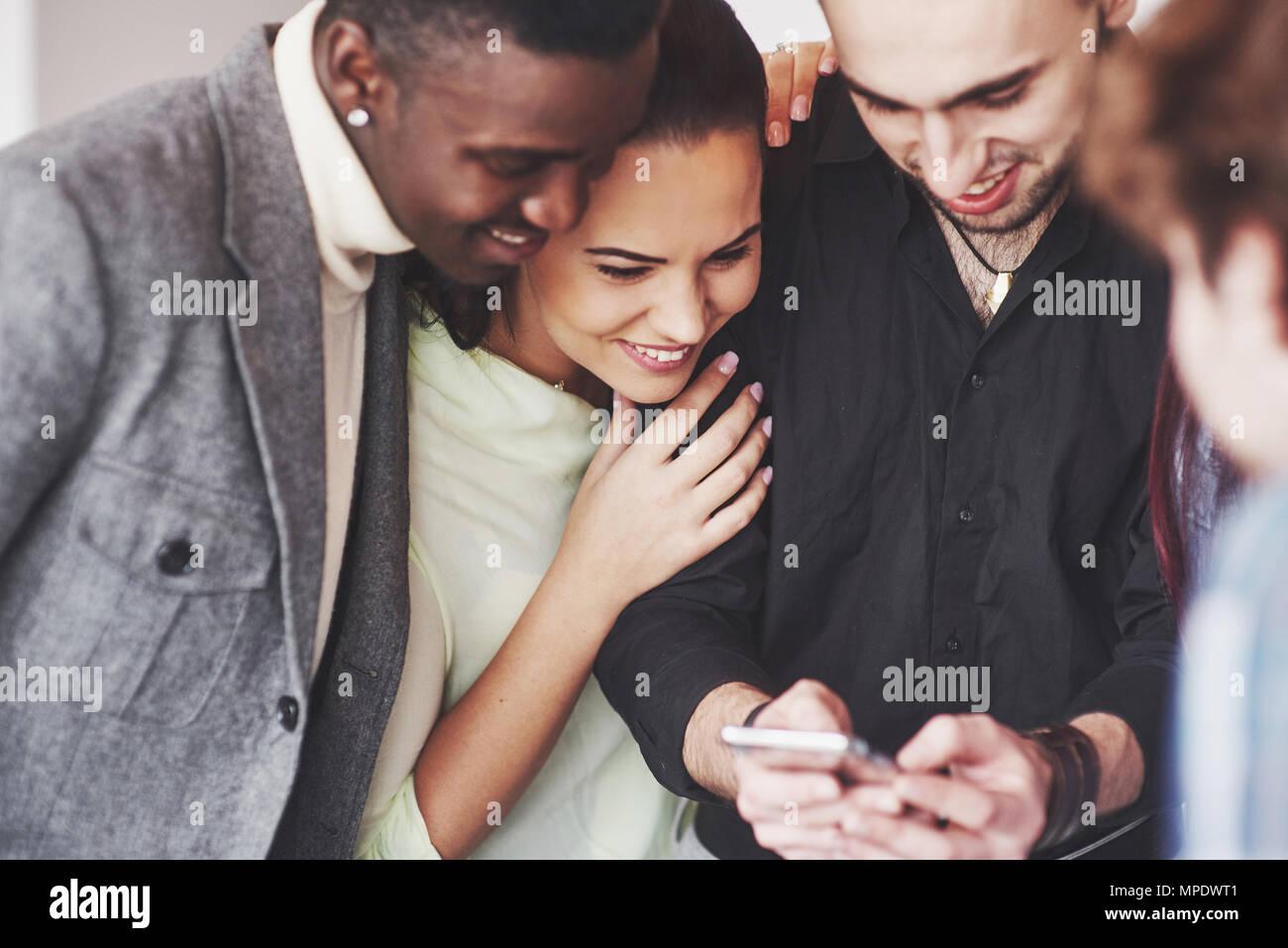 Ritratto di Allegro giovani amici guardando smart phone mentre è seduto al cafe'. Razza mista di persone nel ristorante utilizzando il telefono cellulare Immagini Stock