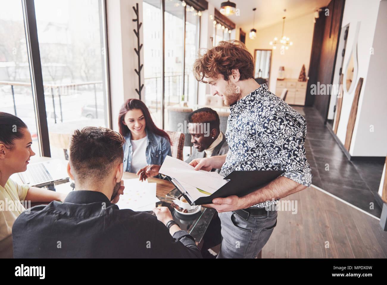La diversità di avvio al lavoro di squadra Riunione di brainstorming Concept. Il team di Business collaboratori condivisione economia mondiale relazione documento portatile.persone che lavorano la pianificazione avvia.Gruppo Giovani Hipsters discutendo Cafe Immagini Stock