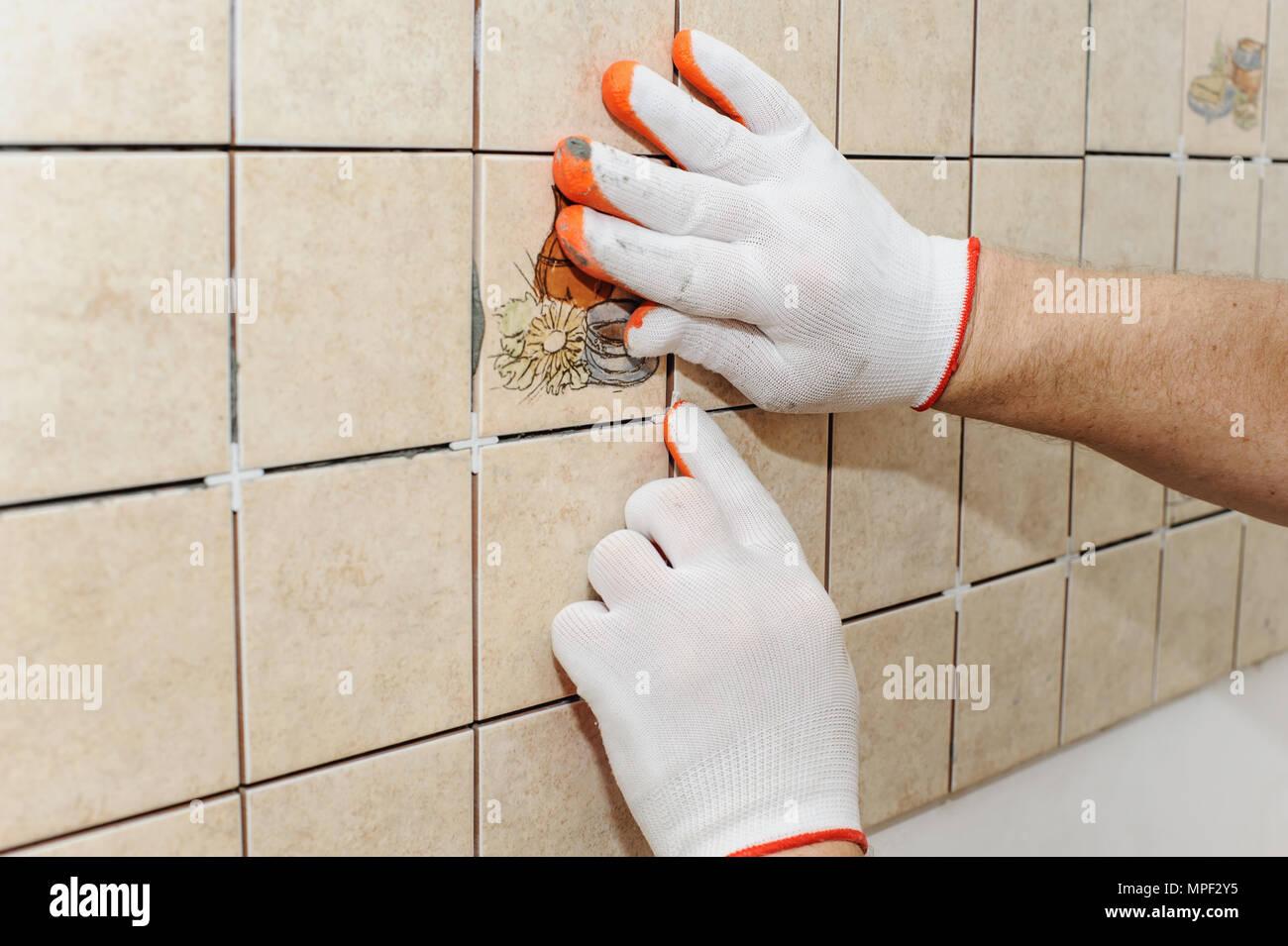Lavoratore mettendo le piastrelle sulla parete in cucina. Le sue ...