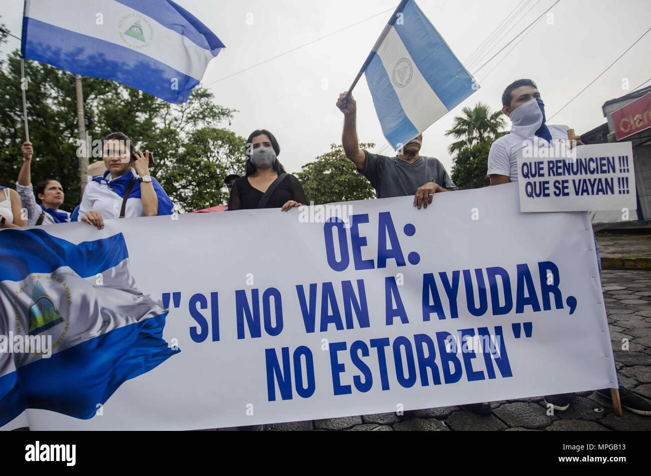 """Managua, Nicaragua. 23 Maggio, 2018. Parecchie persone protestano al di fuori del seminario di Nostra Signora di Fatima con un cartello che recita """"OAS: Se non si ha intenzione di aiutare, non preoccupatevi' a Managua, Nicaragua, 23 maggio 2018. La Nicaragua Conferenza Episcopale, mediatore e wittness presso il National colloqui, ha incoraggiato il Presidente Daniel Ortega per creare un inchiesta internazionale meccanismo per i fatti di violenza si è verificata nel paese durante proteste contro il governo che ha lasciato 76 morti. Credito: Jorge Torres/EFE/Alamy Live News Immagini Stock"""