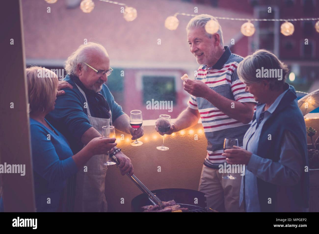 Grigliata bbq e qualche vino per festeggiare un evento. gruppo di persone adulte godetevi lo stile di vita all'aperto in terrazza con vista sulla città. mangiare mangiare e bere un bicchiere di vino Immagini Stock