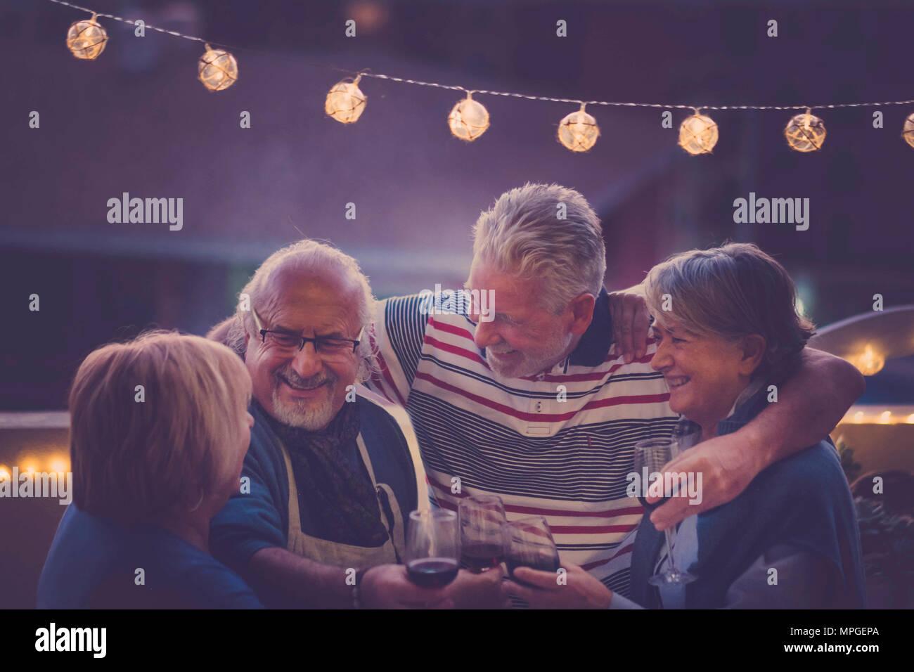 Focus sull'uomo. gruppo di anziani di età adulta facendo parte della notte sul tetto di casa. abbraccio tutti insieme e sorridere e ridere per un attività di nizza Immagini Stock