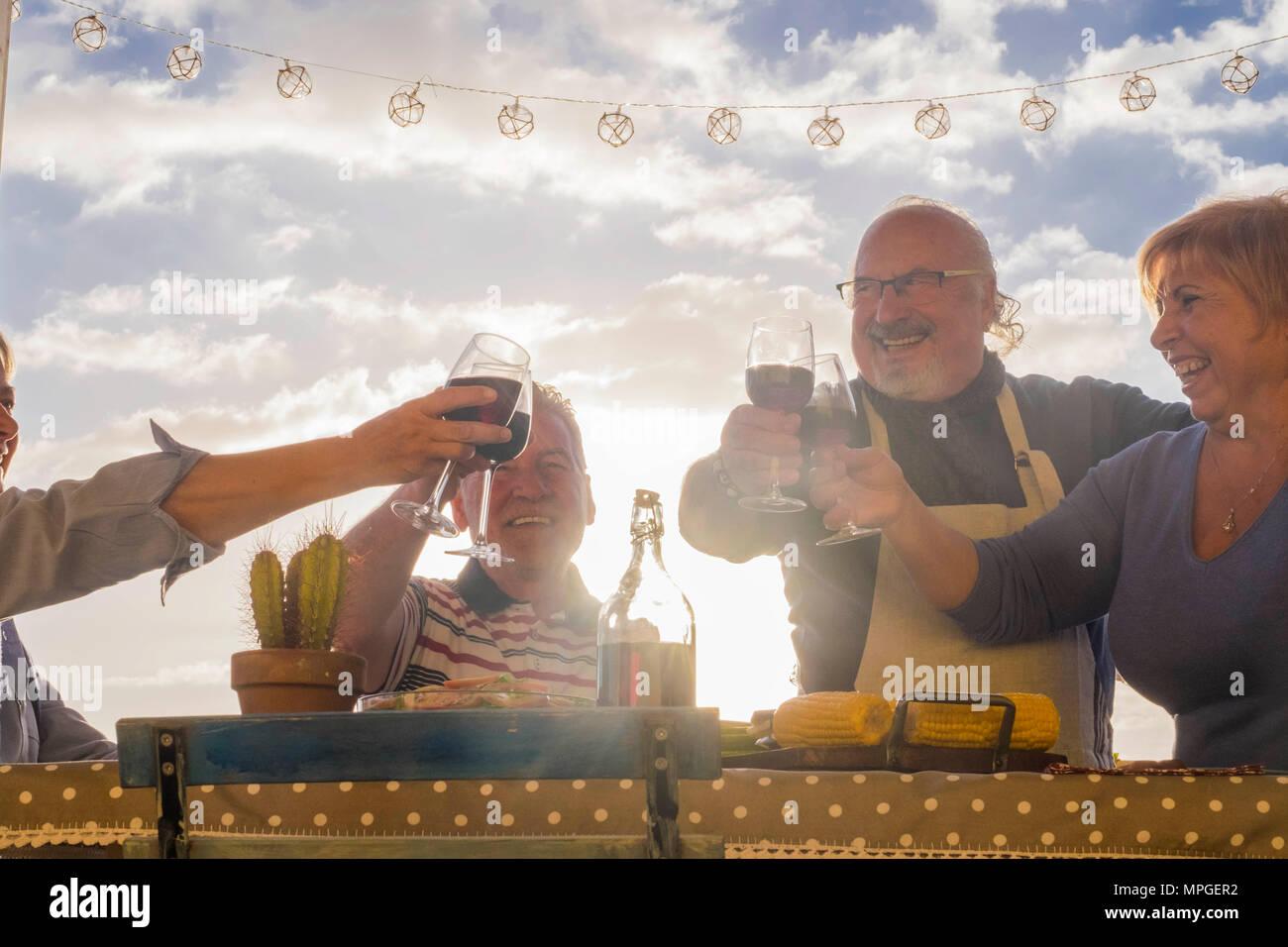 Uomini e donne adulti cheers con vino all'aperto nel patio terrazza tetto per festeggiare in vacanza o compleanno o evento. anziani lifestyle giorno felice vita c Immagini Stock