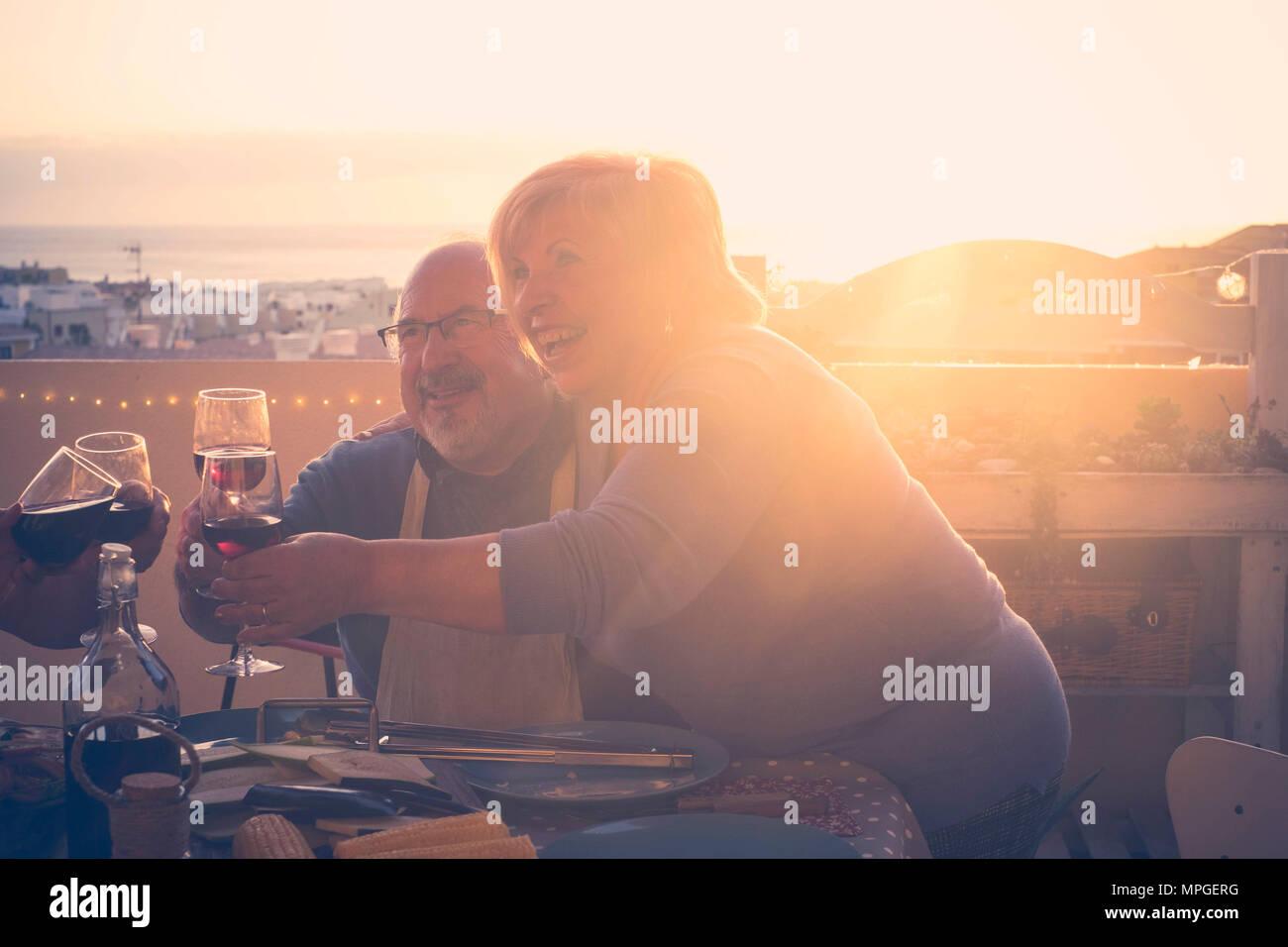 Il gruppo di età compresa tra i senior amici adulti aventi la cena e facendo parte bel tempo in terrazza all'aperto con vino e cibo. avendo divertimento durante la s Immagini Stock